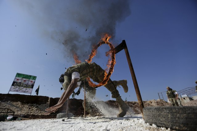 A rebel fighter jumps through a fire loop as he demonstrates his skill during a military display as part of a graduation ceremony at a camp in the north of Hama province, Syria March 31, 2016. (Photo by Khalil Ashawi/Reuters)