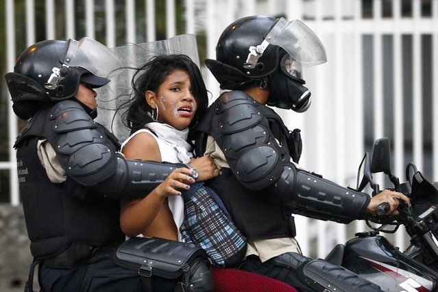 National police transport an anti-government protester detainee during a protest against Nicolas Maduro's government in Caracas March 13, 2014. Venezuela's state prosecutor said on Thursday the death toll from a month of violent protests had risen to 28, after the nation's top court ordered opposition mayors to dismantle barricades set up by street protesters. (Photo by Carlos Garcia Rawlins/Reuters)