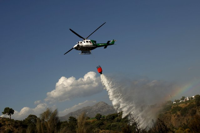 A helicopter drops water over a wildfire in Benahavis, southern Spain, May 19, 2015. (Photo by Jon Nazca/Reuters)