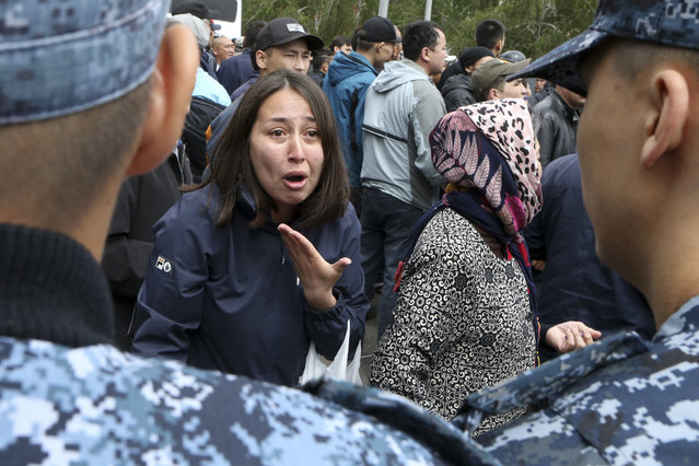 A woman speaks to Kazakh police as they block demonstrators during an anti-government protest during the presidential elections in Nur-Sultan, the capital city of Kazakhstan, Sunday, June 9, 2019. Voters in Kazakhstan are choosing a successor to the president who had led the Central Asian country since independence from the Soviet Union, with a longtime loyalist expected to win easily. (Photo by Alexei Filippov/AP Photo)