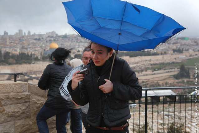 The wind turns a tourist's umbrella out as she braves a winter storm to enjoy the view of the Old City from the Mount of Olives