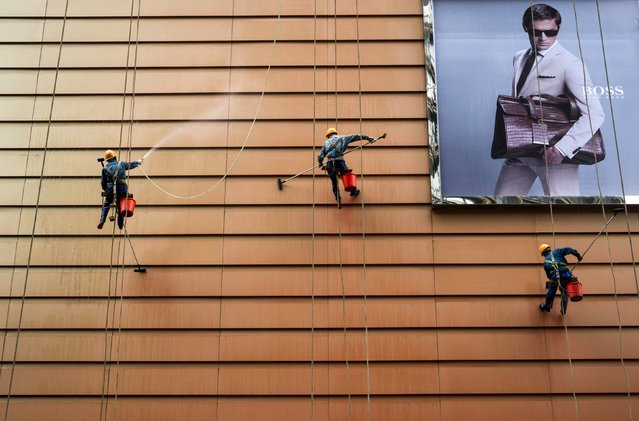 Workers clean the exteriors of a building next to an advertisement in Wuxi, Jiangsu province, China, May 23, 2015. (Photo by Reuters/Stringer)