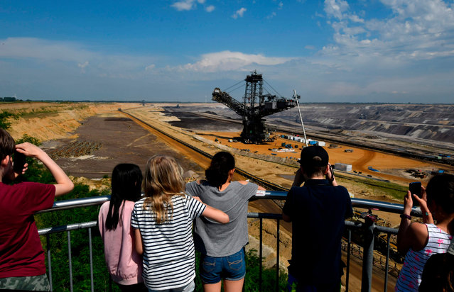 Visitors take a picture of a bucket-wheel excavator used to dig brown coal at the Garzweiler lignite mine near Jackerath, Germany on June 18, 2019. Thousands of climate activists are preparing to blockade the site. (Photo by Ina Fassbender/AFP Photo)