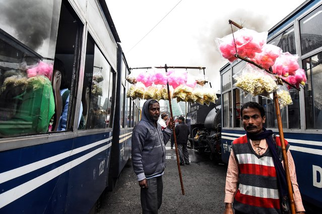 Vendors sell candy floss to passengers as Darjeeling Himalayan Railway trains, which runs on a 2 foot gauge railway and is a UNESCO World Heritage Site, arrive at a station in Ghum, India, June 25, 2019. (Photo by Ranita Roy/Reuters)