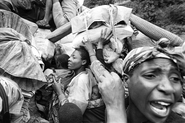 Crowds of refugees near Ruhengeri, Rwanda, desperately try to get on trucks taking them to Kigali, with a great deal of pushing and screaming; 1996. (Photo by Carol Guzy/The Washington Post)