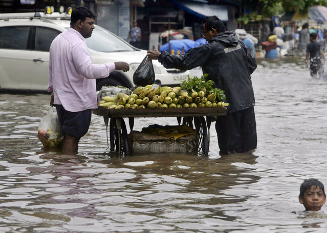 A boy plays as a street vendor attends to a customer in a waterlogged street following heavy rains in Mumbai, India, Tuesday, July 2, 2019. (Photo by Rajanish Kakade/AP Photo)