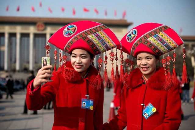 """Hostesses take a selfie with a smartphone as they wait for delegates to wallk out of a session of the Chinese People' s Political Consultative Conference in Beijing on March 4, 2017 China will raise defence spending by """"around seven percent"""" this year as it guards against """"outside meddling"""" in its disputed territorial claims in Asian waters, a top official said on March 4, 2017. (Photo by Nicolas Asfouri/AFP Photo)"""