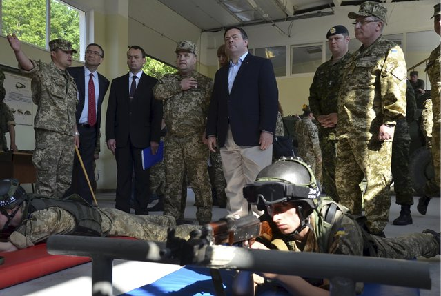 Canadian Defence Minister Jason Kenney (C) and his Ukrainian counterpart Stepan Poltorak (4th L) visit the International Center of Peacekeeping and Security in Yavoriv, outside Lviv, Ukraine, June 27, 2015. The West should not drop its guard over Ukraine, Poltorak said on Friday, saying a build-up of Russian forces in support of separatists showed President Vladimir Putin was bent on seizing control of the country. (Photo by Roman Baluk/Reuters)