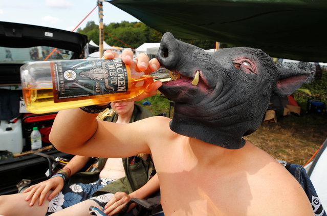A festival goer from the Bavarian town of Diessen near Munich wears a pig mask as he drinks sweet mead, the official mead of the world's largest heavy metal festival, the Wacken Open Air 2019, in Wacken, Germany on August 3, 2019. (Photo by Wolfgang Rattay/Reuters)