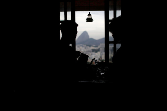 """A worker serves coffee to a guest at Pousada Favelinha (Little favela) hostel kitchen in Pereira da Silva favela, in Rio de Janeiro, Brazil, April 29, 2016. Hostels in a few of Rio's more than 1,000 slums serve not only as a cheap housing alternative for the more adventurous among the estimated 500,000 foreign tourists expected to arrive for the Olympics in August. The establishments also open up the rich culture of the city's shantytowns for travellers, giving them a glimpse into once """"no-go"""" areas where about one-fifth of Rio's population lives. (Photo by Pilar Olivares/Reuters)"""
