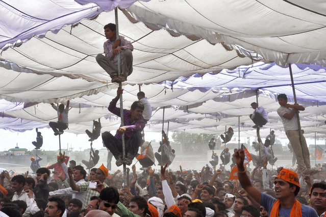 Supporters of Hindu nationalist Narendra Modi, the prime ministerial candidate for India's main opposition Bharatiya Janata Party (BJP), climb over the poles of a temporary tent to get a glimpse of Modi during an election campaign rally at Mathura in the northern Indian state of Uttar Pradesh April 21, 2014. (Photo by K. K. Arora/Reuters)