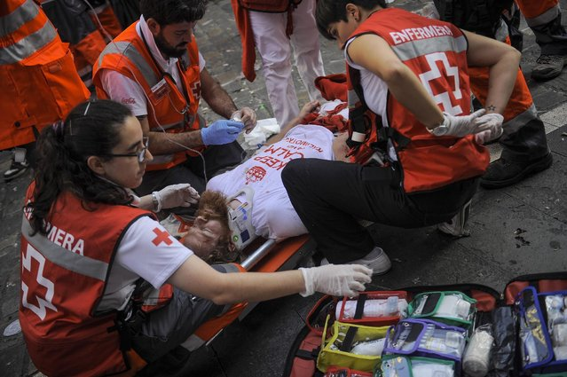 "An injured runner is attended by a medical assistant after being gored by a ""Jandilla"" fighting bull during the running of the bulls at the San Fermin Festival, in Pamplona, Spain, Tuesday, July 7, 2015. (Photo by Alvaro Barrientos/AP Photo)"