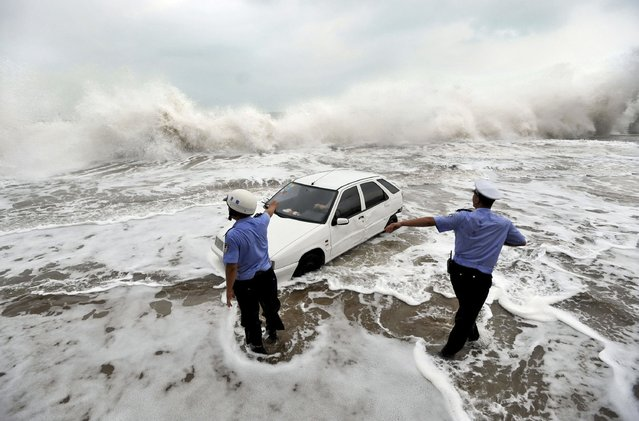 Policemen gesture to a driver stranded in a car on a flooded road as waves are whipped up by typhoon Bolaven in Qingdao, Shandong province, August 28, 2012. Gales and downpours brought by typhoon Bolaven swept through parts of northeast China from Tuesday evening to Wednesday, flooding cities and delaying flights, Xinhua News Agency reported. (Photo by Reuters/China Daily)