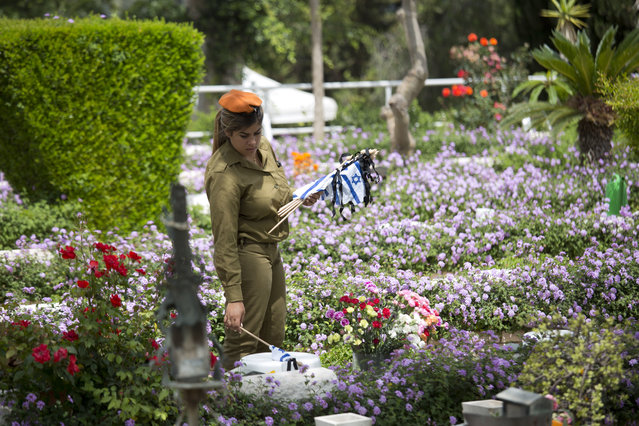 An Israeli soldier places small flags with black ribbons on graves of fallen soldiers on the eve of memorial Day in Kiryat Shaul military cemetery in Tel Aviv, Israel, Tuesday, May 10, 2016. (Photo by Ariel Schalit/AP Photo)