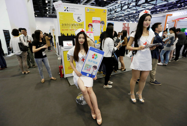 Models dressed as nurses promote a mobile medical service to home during the Global Mobile Internet Conference (GMIC) in Beijing, China, April 28, 2016. (Photo by Jason Lee/Reuters)