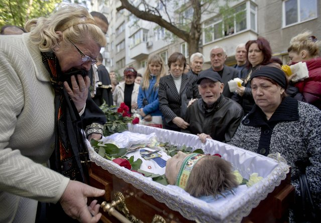 Relatives cry around the coffin of 17 year-old Vadim Papura during a religious service outside his apartment block, in Odessa, Ukraine, Tuesday May 6, 2014. Papura died after jumping out of the burning trade union building in an attempt to escape Friday's fire that killed most of the 40 people that died after riots erupted last Friday. (Photo by Vadim Ghirda/AP Photo)