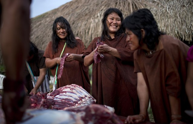 In this June 22, 2015 photo, Ashaninka Indian women skim fat from the meat of a cow in the village Otari Nativo, Pichari, Peru. The cow was donated by municipal authorities to mark the 44th anniversary of the community's founding. The community's men then smoked the large amounts of meat for festival-goers to consume. (Photo by Rodrigo Abd/AP Photo)