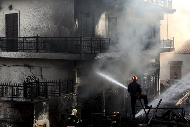 A firefighter tries to extinguish a fire at a building at the town of Neapoli in the region of Laconia in Peloponnese, southern Greece July 17, 2015. (Photo by Vassilis Konstantopoulos/Reuters/Intimenews)