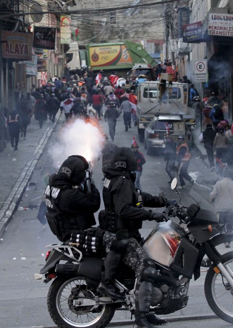 Riot police man shoot tears gas against Potosi demonstrators during clashes in La Paz, July 17, 2015. Hundreds of demonstrators  of Potosi demanded to have a meeting with President Evo Morales to discuss about the industrialization of their region in their fifth day of protest in La Paz, according to local media. (Photo by David Mercado/Reuters)