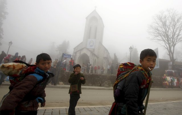 Hmong boy carry their brothers past a Catholic church on a foggy day after Sunday Mass, in Vietnam's northern resort town of Sapa, north of Hanoi, February 21, 2016. (Photo by Reuters/Kham)