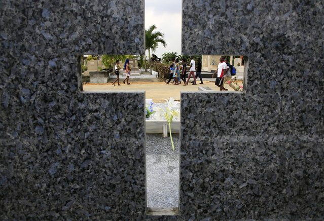 """People are seen through the cross shape cut out in a headstone as they visit the Williamsville cemetery in Abidjan, Ivory Coast, or Cote D'Ivoire, during All Saints' Day 01 November 2019. Each year the feast of """"Toussaints"""", or All Saints' Day, moves the people in the different parishes to visit the cemeteries to deposit wreaths and flowers on the tombs of their late beloved. Faithful take advantage of the All Saints' Day for prayers to God and all the saints recognized by the Christian Church. (Photo by Legnan Koula/EPA/EFE)"""