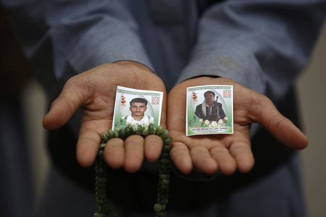 A Shiite rebel known as a Houthi displays pictures of his relatives, who were killed in a recent a car bomb attack, during their funeral in Sanaa, Yemen, Wednesday, July 22, 2015. (Photo by Hani Mohammed/AP Photo)