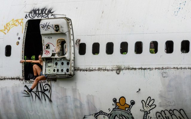 """Tourists take photos in an abandoned aircraft in the suburbs of Bangkok on October 9, 2019. The area, known as the """"airplane graveyard"""", has become a tourist attraction in the Thai capital. (Photo by Mladen Antonov/AFP Photo)"""