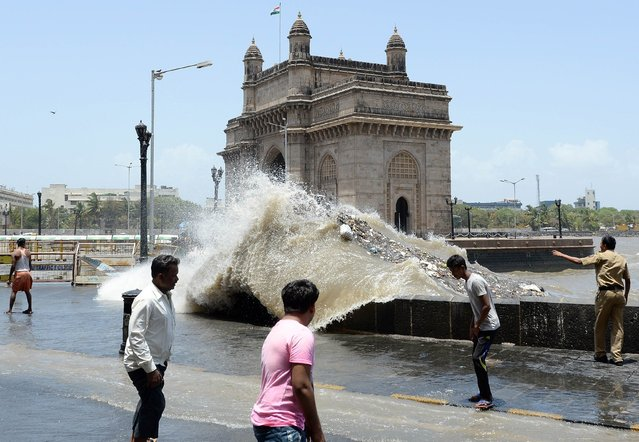 An Indian policeman (R) warns onlookers as waves come ashore during high tide near the Gateway of India  in Mumbai on June 13, 2014. The Indian Meteorological Department (IMD) has declared the start of the monsoon season, predicting below-average rainfall. The monsoon season, which runs from June to September, accounts for about 80 percent of India's annual rainfall, vital for a farm economy which lacks adequate irrigation facilities. (Photo by Indranil Mukherjee/AFP Photo)
