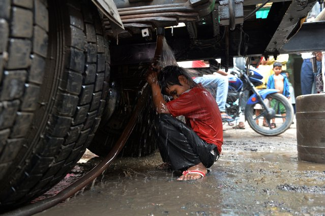 An Indian child sits underneath a gushing outlet of a water distribution tanker in New Delhi on June 16, 2014. The sprawling Indian capital, with a population of more than 16 million sweltering in 45-47 degree summer heat, relies on four neighbouring states for its water – Haryana, Uttar Pradesh, Punjab and Uttarakhand. (Photo by Chandan Khanna/AFP Photo)