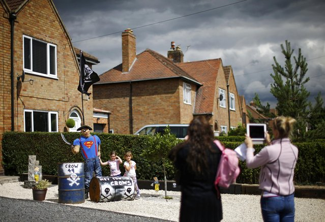 Children have their photographs taken with a pirate scarecrow during the Scarecrow Festival in Heather, Britain July 29, 2015. (Photo by Darren Staples/Reuters)