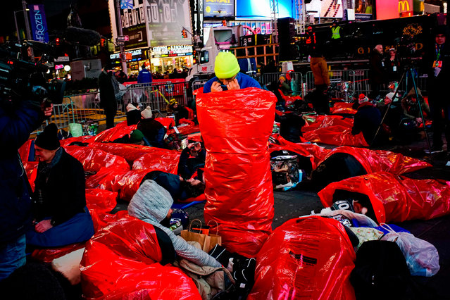 People get ready to sleep outside while taking part in The World's Big Sleep Out event in Times Square on December 7, 2019 in New York. (Photo by AFP Photo/Stringer)