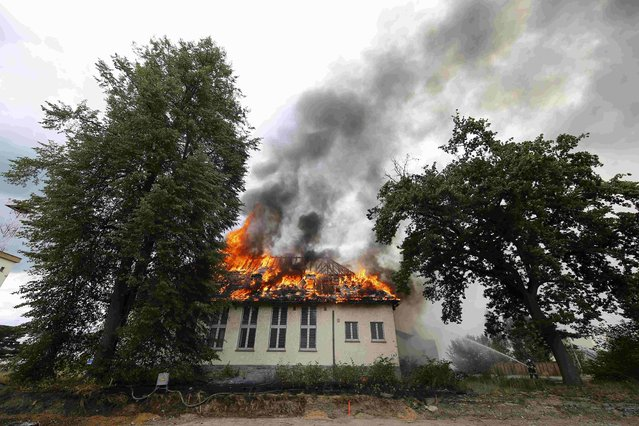 A firefighter uses a water hose to extinguish a building after a fire broke out at a former U.S. airfield in Erlensee, Germany July 30, 2015. About 250 firefighters attempted to control the fire in the historical ensemble of buildings, part of the country's national heritage. (Photo by Kai Pfaffenbach/Reuters)