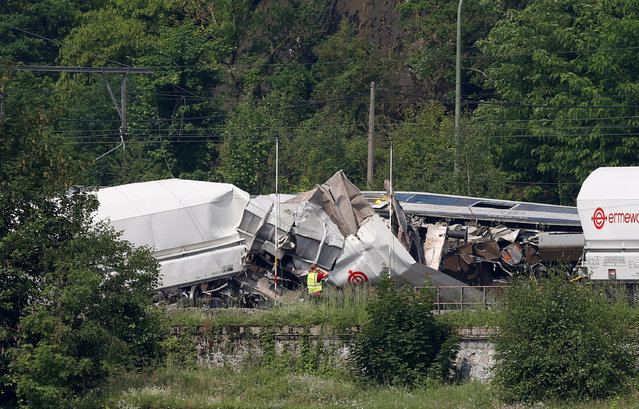 An official inspects the wreckage of a passenger train after it crashed into the back of a freight train in the eastern Belgian municipality of Saint-Georges-Sur-Meuse, June 6, 2016. (Photo by Francois Lenoir/Reuters)