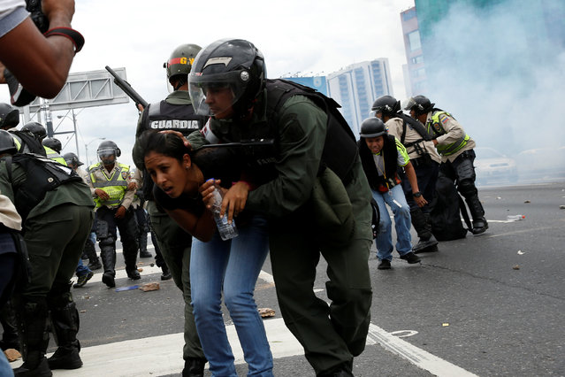A Venezuelan National Guard covers a woman as they run away from tear gas during a rally to demand a referendum to remove President Nicolas Maduro in Caracas, Venezuela, June 7, 2016. (Photo by Carlos Garcia Rawlins/Reuters)