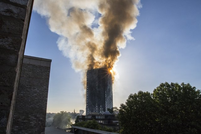 Smoke billows from a high-rise apartment building in west London Wednesday, June 14, 2017. A massive fire raced through the building early Wednesday, emergency officials said. (Photo by Rick Findler/PA Wire via AP Photo)
