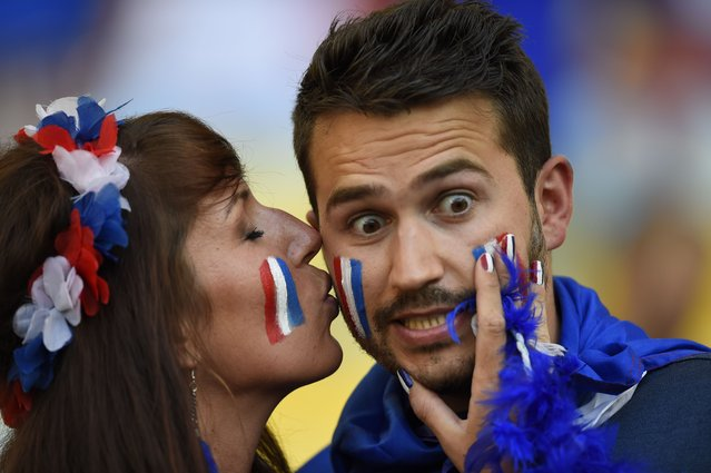 French supporters kiss prior to the start of a Group E football match between Ecuador and France at the Maracana Stadium in Rio de Janeiro during the 2014 FIFA World Cup on June 25, 2014. (Photo by Odd Andersen/AFP Photo)