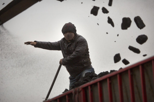 In this Tuesday, November 3, 2015, photo, a worker guides a conveyor as it loads coal into a trailer truck at a coal mine near Ordos in northern China's Inner Mongolia Autonomous Region. The world's biggest coal users - China, the United States and India - have boosted coal mining in 2017, in an abrupt departure from last year's record global decline for the heavily polluting fuel and a setback to efforts to rein in climate change emissions. (Photo by Mark Schiefelbein/AP Photo)