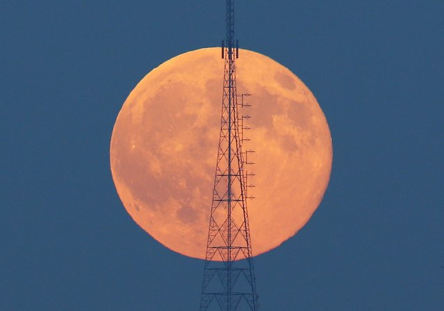 A full moon, known as the Blue Moon, rises behind a telecommunication tower over the Camlica Hill in Istanbul, Turkey, July 31, 2015. (Photo by Murad Sezer/Reuters)