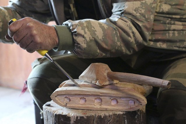 Abu Khalil, a 47-year-old Free Syrian Army fighter who is also a visual artist and decorator, carves a tank out of wood at Jabal al-Turkman in Latakia province January 20, 2015. (Photo by Alaa Khweled/Reuters)