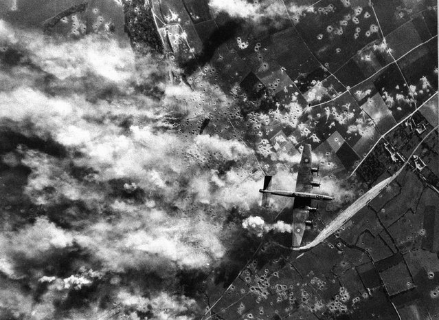An RAF Halifax over the target a large concrete structure in the Pas De Calais area in France on July 6, 1944 during daylight attack by Bomber Command where bursting bombs send clouds of smoke and dust into the Air. (Photo by AP Photo)