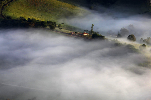 Fog sourrounds a farm in the mountains in Goncalves, in the state of Minas Gerais in southwestern Brazil, April 18, 2014. (Photo by Paulo Whitaker/Reuters)