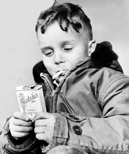 """Michael Miller, 5, of Fargo, N.D., """"puffs"""" on one of his last candy cigarettes, March 14, 1953.  North Dakota's governor signed a bill passed by the legislature forbidding the sale or possession of candy packaged to resemble cigarettes. The law is effective July 1.  Violation is punishable by a fine of up to $1,000 and 90 days in jail. (Photo by AP Photo)"""