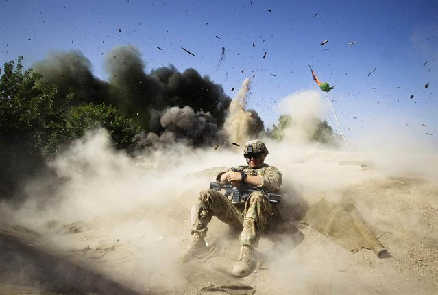 U.S. Army Pvt. Jake Beaudoin takes cover during a controlled detonation to clear an area for setting up a checkpoint, in Zahri district of Kandahar province, southern Afghanistan, May 31