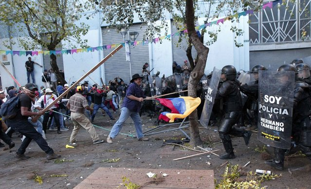 Demonstrators holding an Ecuadorean flag clash with police during a protest in Quito, Ecuador, August 13, 2015. (Photo by Guillermo Granja/Reuters)