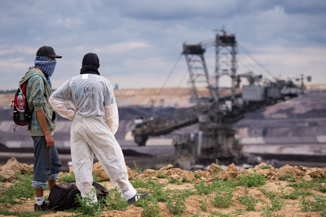 Protestors look at a huge bucket-wheel excavator as they arrive  for a demonstration  at the open-pit coal mine near Garzweiler, western Germany Saturday August 15, 2015. Several hundred environmental activists have stormed a lignite mine in western Germany to protest against the use of coal for electricity production. (Photo by Marius Becker/DPA via AP Photo)