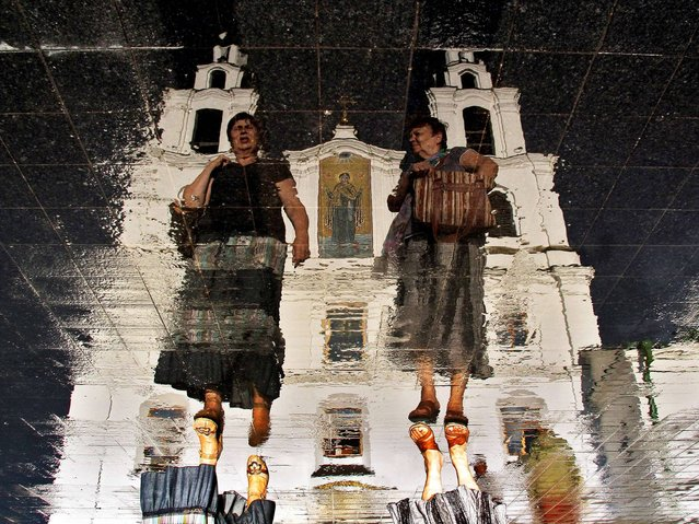 Two women walking in front of Svyato-Dukhov (Holy Spirit ) Orthodox cathedral are reflected in the wet tablets of a roadway in the Belarus capital Minsk, on July 20, 2014. (Photo by Sergei Gapon/AFP Photo)