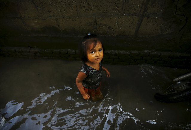 A girl walks through floodwaters caused by the heavy rainfall flowing from the swollen Bagmati River, which entered a slum in Kathmandu, Nepal August 17, 2015. (Photo by Navesh Chitrakar/Reuters)