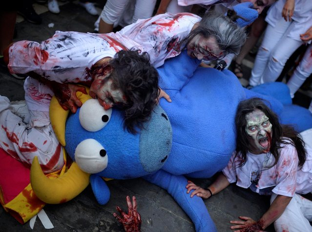Revellers dressed as zombies bite a bull figure during an enactment of the running of the bulls a day before the start of the San Fermin festival in Pamplona, northern Spain, July 5, 2016. (Photo by Vincent West/Reuters)