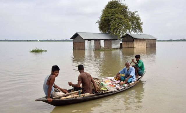 An Indian muslim vendor sells ornaments and toys from a boat on the eve of Eid Al-Fitr at the flood affected Balimukh, in the Morigaon district of the northeastern state of Assam on July 6, 2016. Continuous rain for the last couple of days has inundated seven districts of Assam, affecting more than 90,000 people in the second wave of floods in Assam state. (Photo by Biju Boro/AFP Photo)