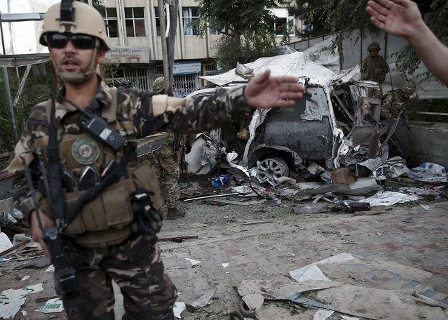 Members of Afghan security forces keep watch in front of a damaged car that belongs to foreigners after a bomb blast in Kabul, Afghanistan August 22, 2015. (Photo by Ahmad Masood/Reuters)